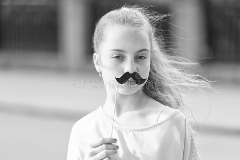 Loving her mustache. Little girl with fake mustache. Cute child holding mustache props on stick. Having fun with. Photobooth party mustache royalty free stock images