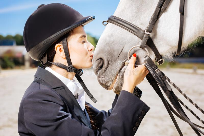 Loving horsewoman with red nail art kissing her white horse. Loving horsewoman. Loving professional horsewoman with red nail art kissing her beautiful white royalty free stock photos