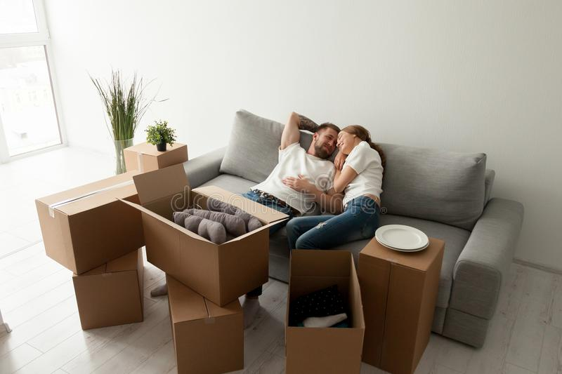 Loving husband lying together on sofa in first shared flat royalty free stock images