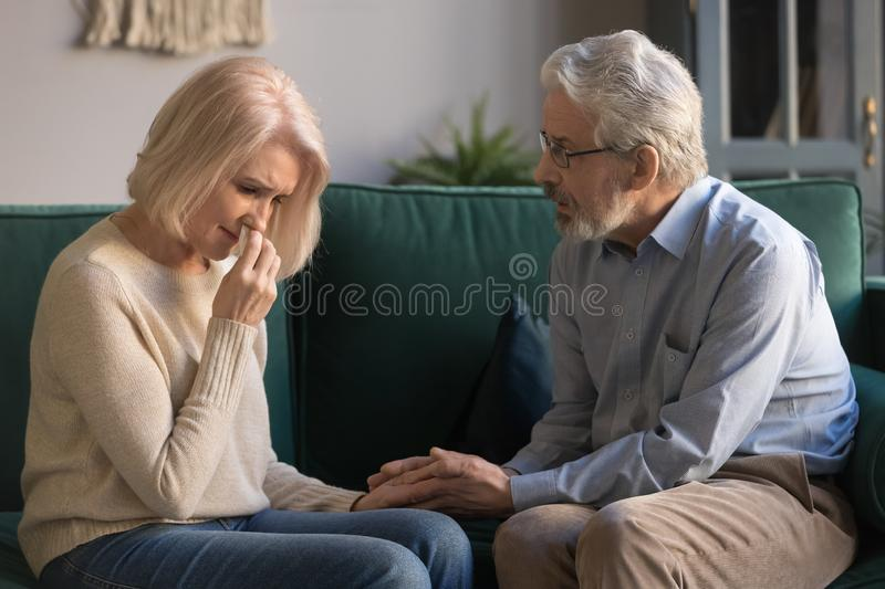 Loving kind old husband consoling comforting sad crying grieving wife. Loving kind old husband consoling comforting sad crying grieving middle aged wife, senior royalty free stock photo