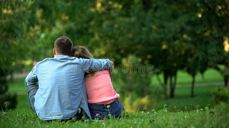Loving male and female hugging sitting on grass in park, couple togetherness. Stock photo stock image