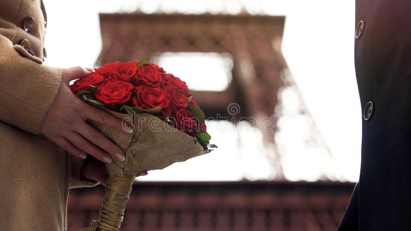 Loving man giving beautiful bouquet of scarlet roses to his sweetheart, love royalty free stock photos