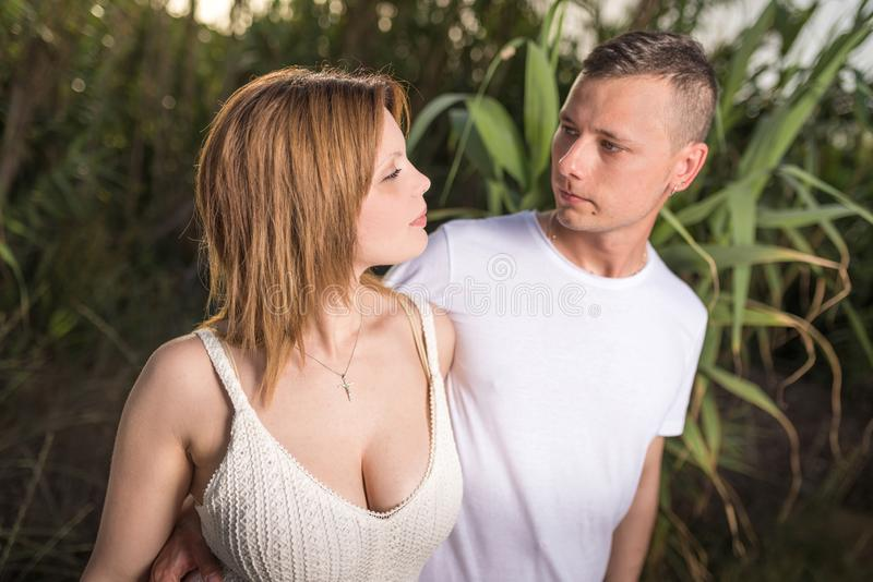 Loving man and happy woman in a spring blooming park. Loving men and happy women in a spring blooming park. Happy mature couple in love embracing outdoor stock image
