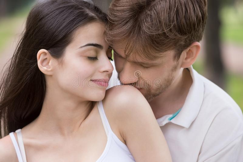 Loving man kissing woman shoulder with tenderness in park royalty free stock image