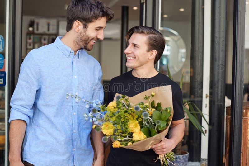 Loving mannenkooi-parelbeugel die uit flora en fauna komt met een bundel bloemen royalty-vrije stock foto's