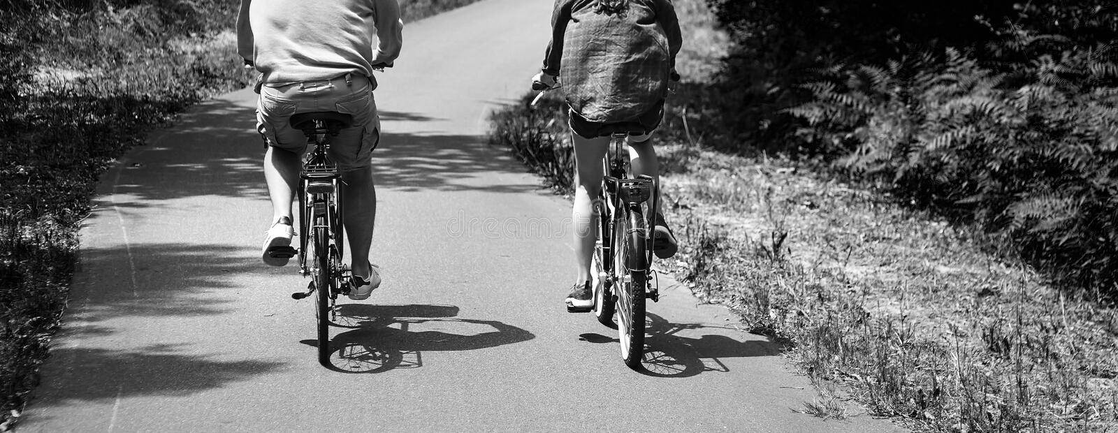 Loving married couple riding on bicycles. A man in shorts and a woman in a shirt. View from the back. Bike ride in the nature royalty free stock photography