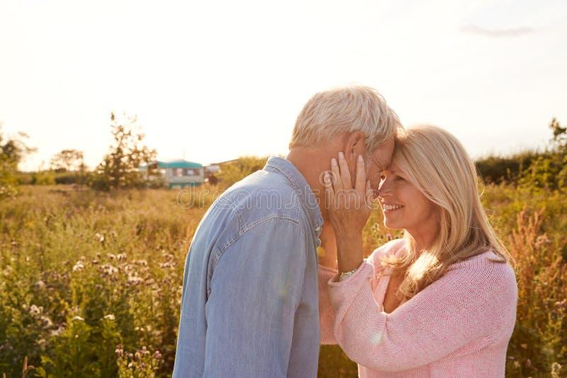 Loving Mature Couple in Countryside Head tegen Flaring Sun stock afbeelding