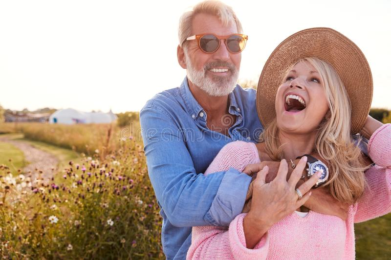 Loving Mature Couple in Countryside Hugging Against Flaring Sun royalty-vrije stock fotografie
