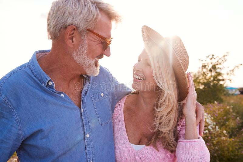 Loving Mature Couple in Countryside Hugging Against Flaring Sun stock foto