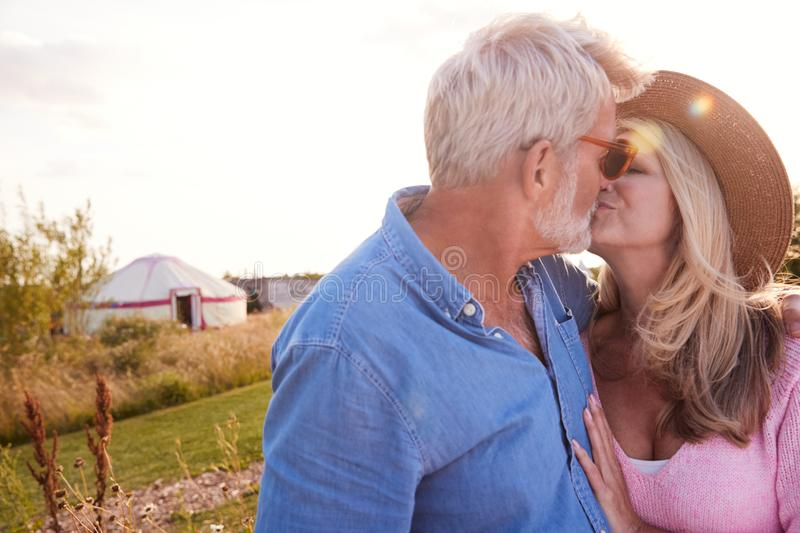 Loving of Mature Couple in Countryside Kissing against Flaring Sun stock foto