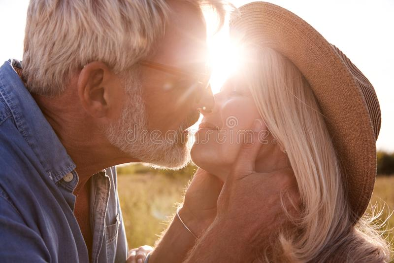 Loving Mature Couple In Countryside About To Kiss Against Flaring Sun stock images