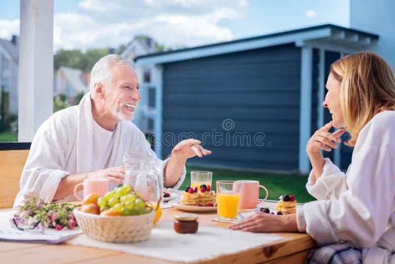 Loving mature couple eating pancakes with fruits and drinking orange juice stock photos