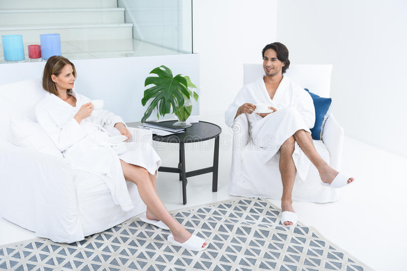 Loving mature couple enjoying day spa. They love coming to spa. Beautiful adult couple talking while relaxing in spa, drinking tea and sitting in white armchairs stock image