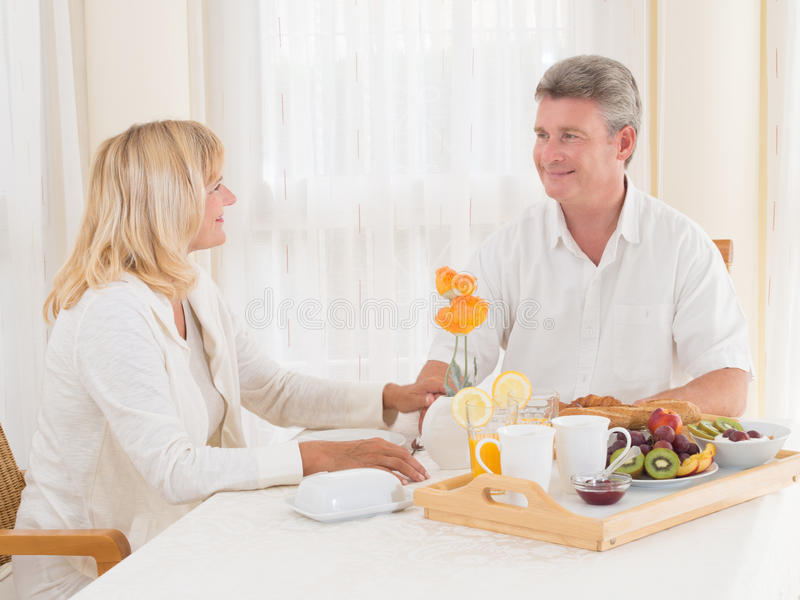 Loving mature couple enjoying a healthy breakfast smiling at each other stock images