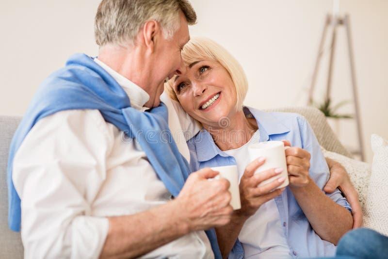 Loving mature couple enjoying morning tea at autumn day stock photo