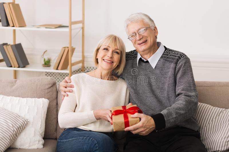 Loving Mature Couple With Gift Box Looking At Camera stock photography