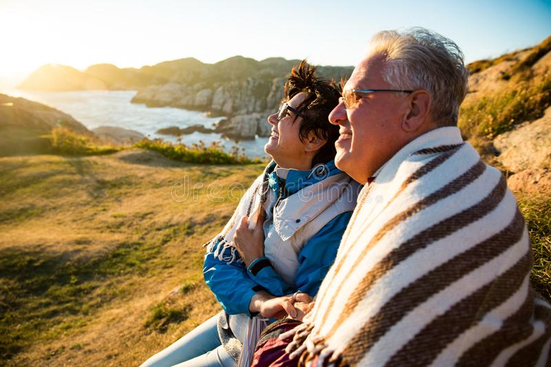 Loving mature couple hiking, sitting on windy top of rock royalty free stock photos