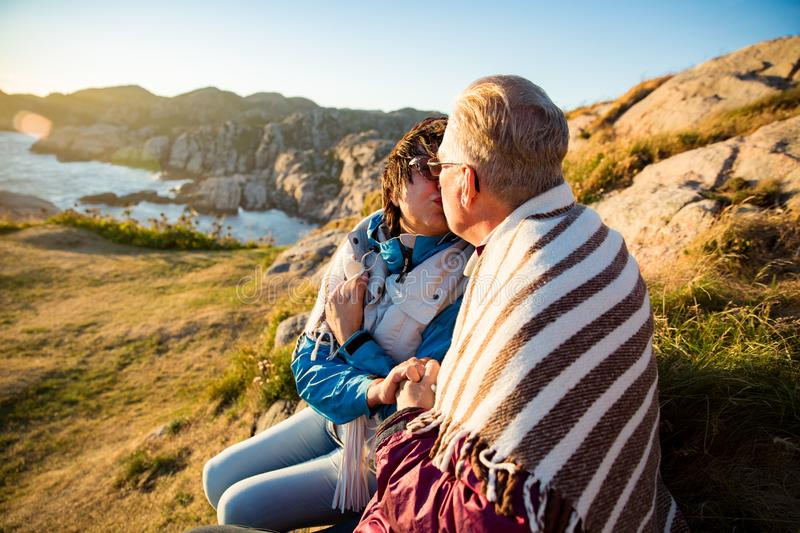 Loving mature couple hiking, sitting on windy top of rock royalty free stock photography