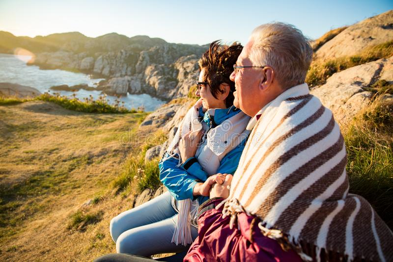 Loving mature couple hiking, sitting on windy top of rock stock image