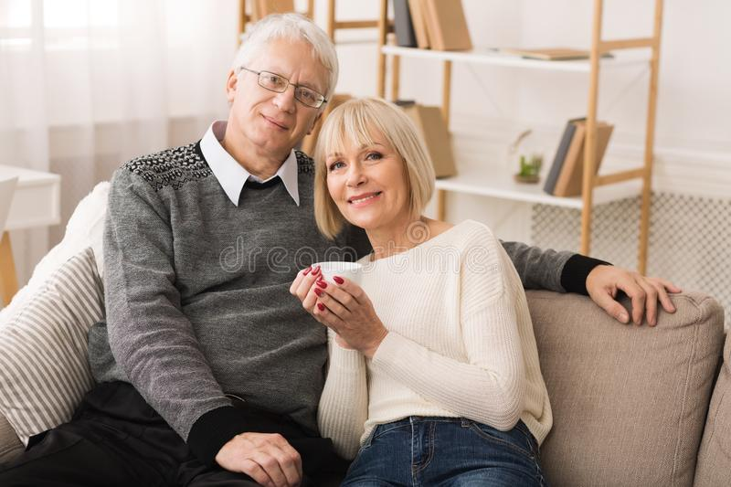 Loving Mature Couple Resting On Sofa And Looking At Camera stock photography