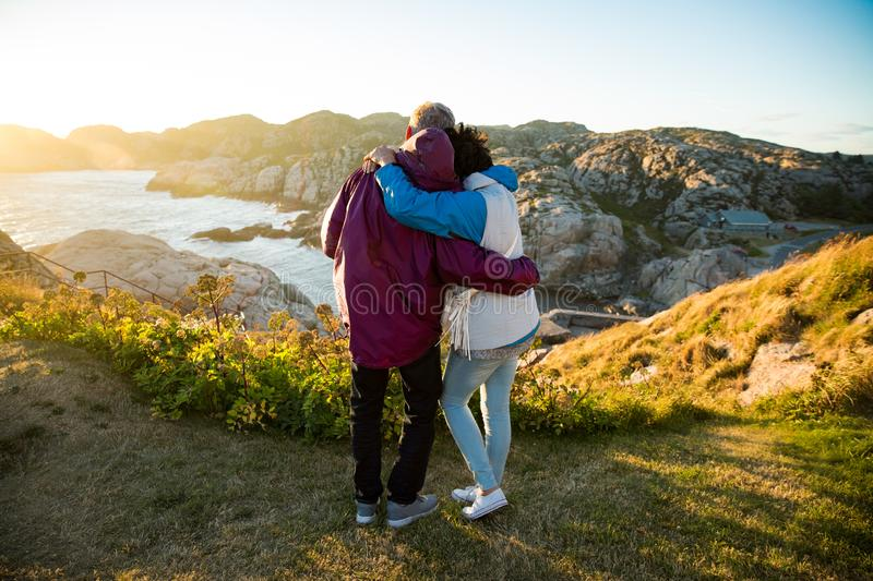 Loving mature couple traveling, standing on the top of rock, exploring stock photography