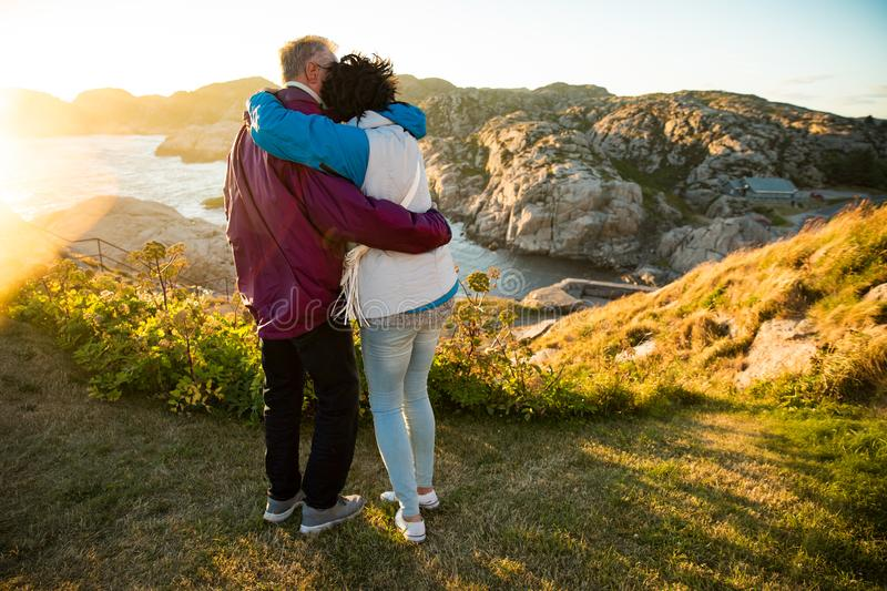 Loving mature couple traveling, standing on the top of rock, exploring royalty free stock image