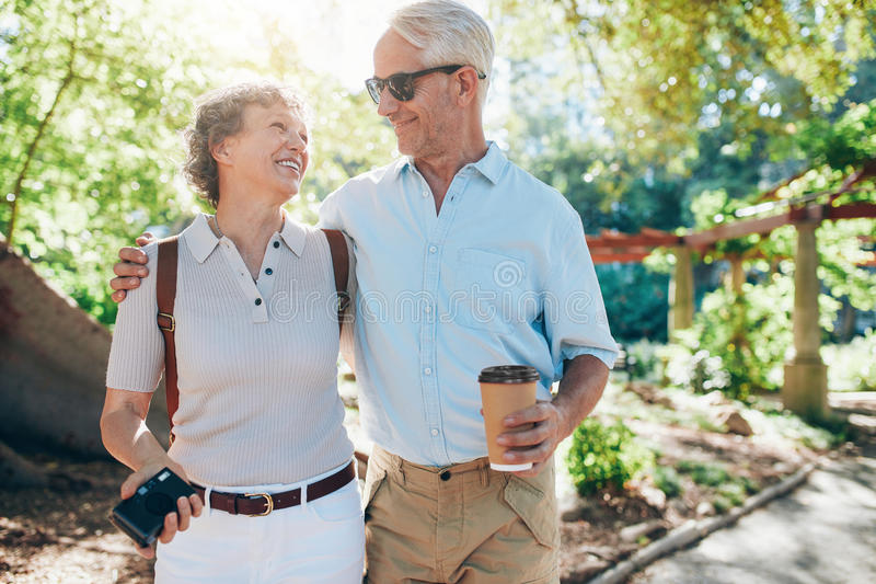 Loving mature couple walking together in a park stock photo