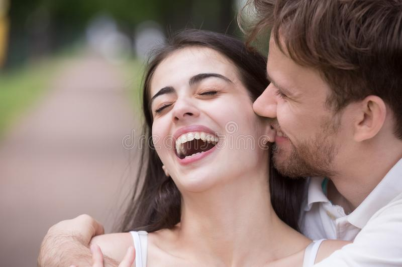 Loving man tickling and embracing laughing woman outdoors stock image