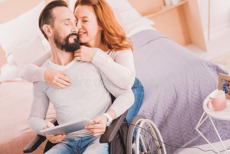 Loving mid aged woman supporting his disabled man stock photography