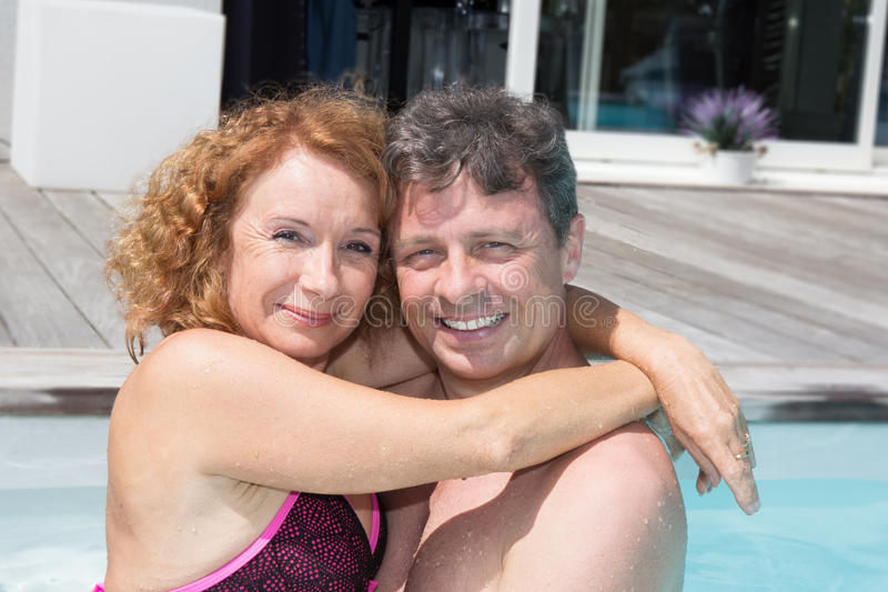 Loving middle aged couple spending romantic time by pool stock photos