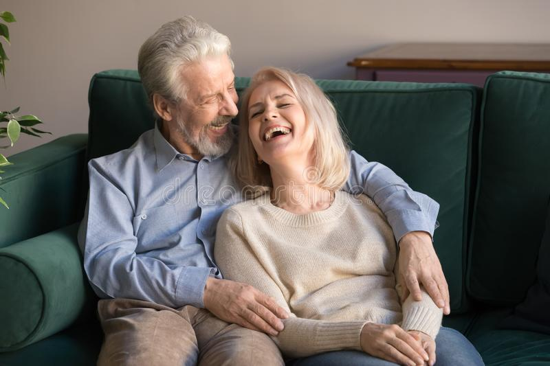 Loving middle aged husband embracing laughing wife, sitting on couch. Loving middle aged husband embracing laughing wife, grey haired couple relaxing, sitting on stock photography