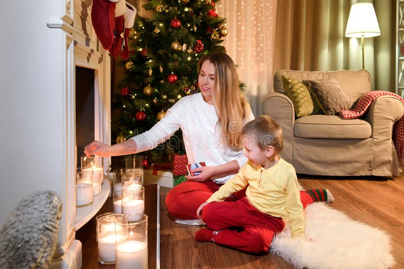 Loving mom is lighting some candles on a fireplace royalty free stock images
