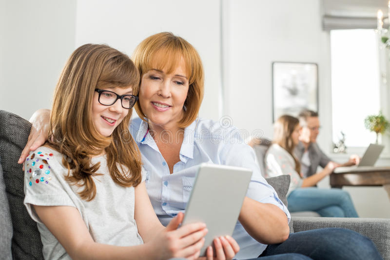 Loving mother and daughter using tablet PC with family sitting in background at home royalty free stock image