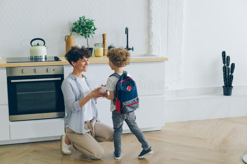 Loving mother giving lunch box to boy with school bag in kitchen smiling. Loving mother smiling women is giving lunch box to small boy with school bag in kitchen stock images