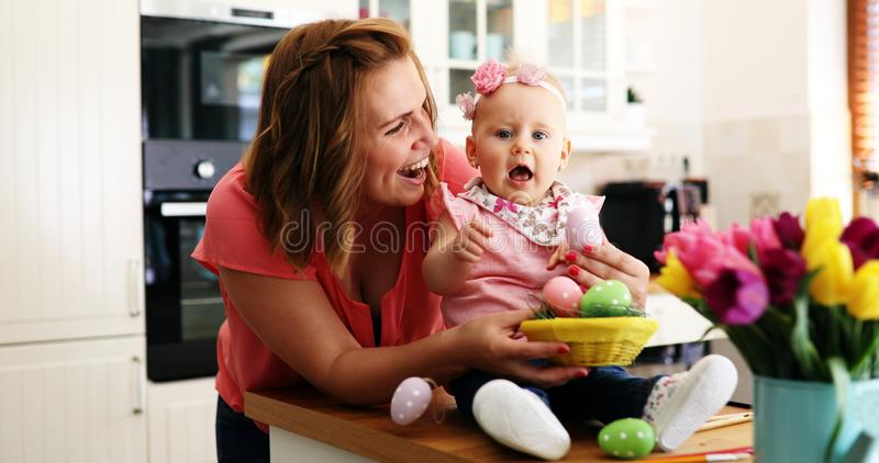 Mother and her baby painting easter eggs royalty free stock photo