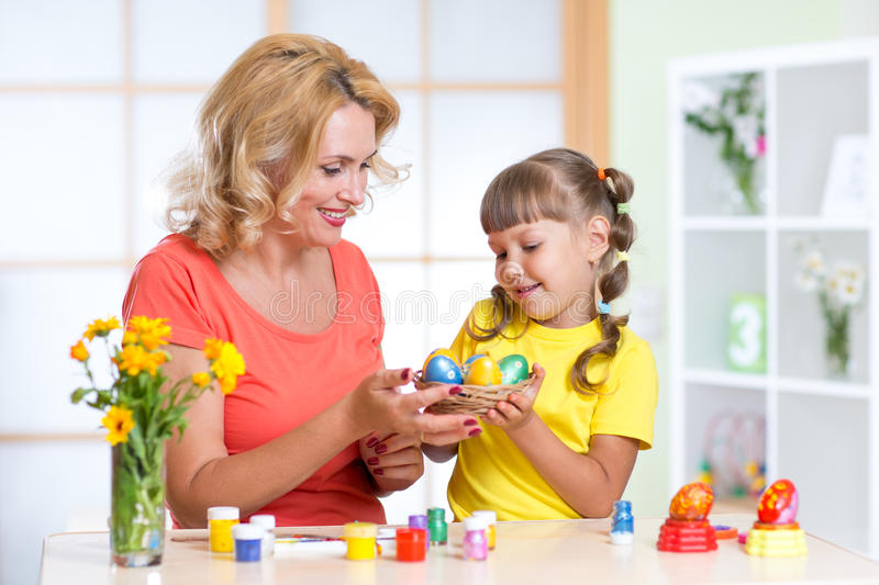 Loving mother and her child painting easter eggs stock photography