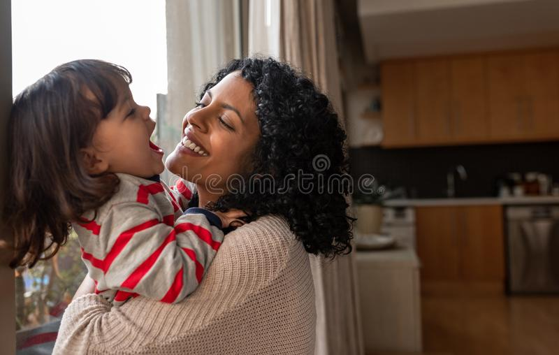 Loving mother hugging her laughing little daughter at home stock image
