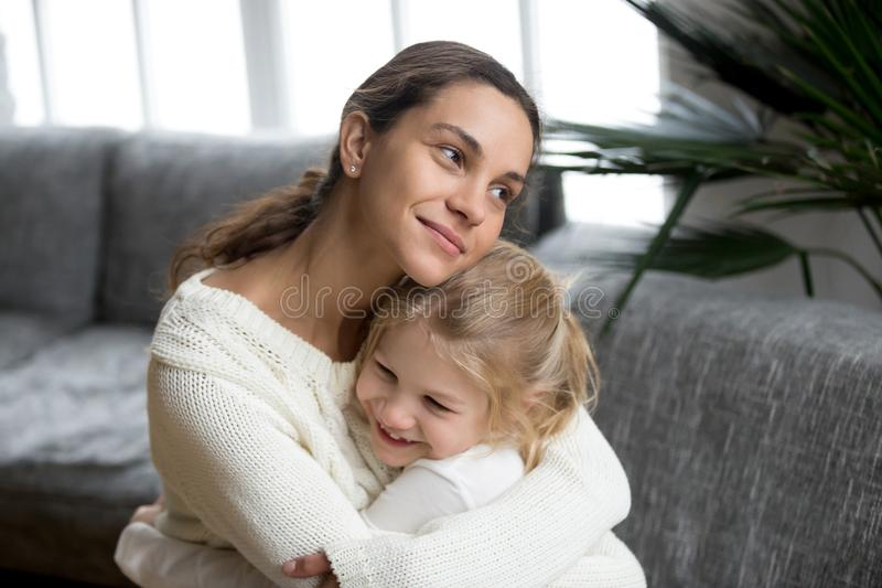Loving mother hugging little daughter showing love, care and sup. Loving single mother hugging cute little daughter showing love care support, happy women stock photos