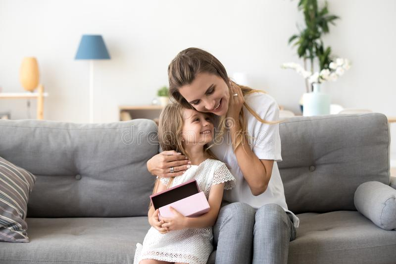 Loving mother hugging little daughter sitting together on sofa stock photos