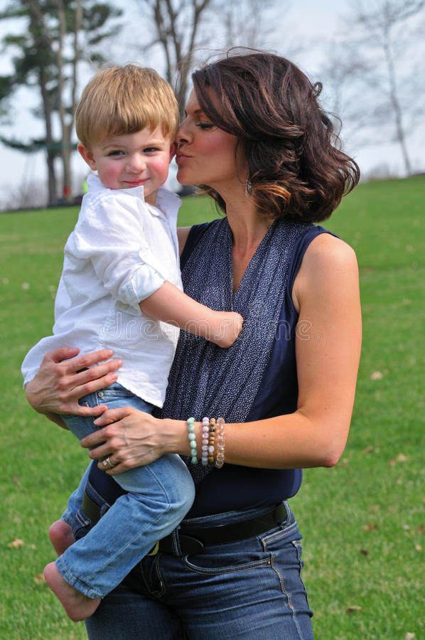 Loving mother kissing her child royalty free stock photography