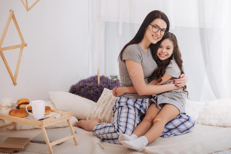 Loving mother and little daughter enjoying weekend at home stock photo