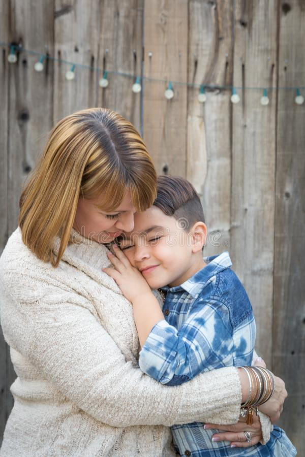 Mother and Mixed Race Son Hug Near Fence. Loving Mother and Mixed Race Son Hug Near Fence royalty free stock photo