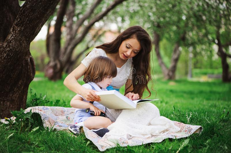 Loving mother reading book to toddler son outdoor on picnic in spring or summer park royalty free stock photo
