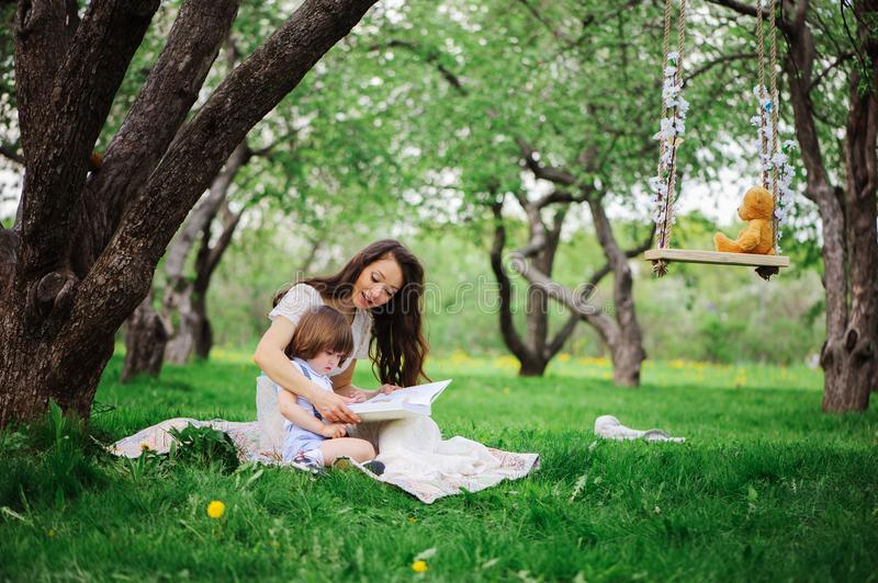 Loving mother reading book to toddler son outdoor on picnic in spring or summer park. Happy family and mothers day concept royalty free stock images