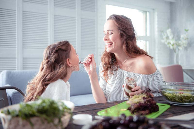 Loving mother smiling while giving her cute girl some chocolate paste stock images