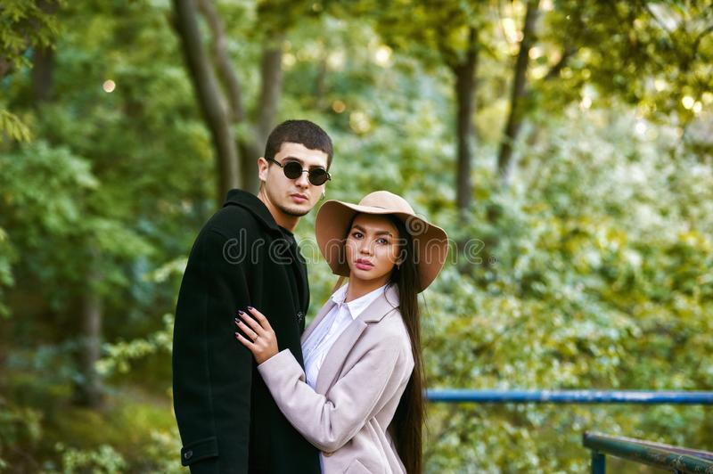 A loving multi-ethnic couple on a walk in the city Park on an autumn day . royalty free stock photography