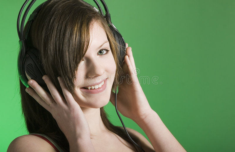 Loving the music. Model with earphones on is loving the music. Horizontal orientation. Copy space on green background stock photo