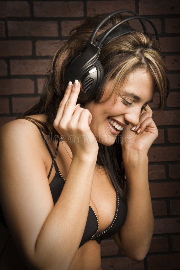 Loving the music. Young woman is grooving to the music. Model is wearing a bra and headset. Portrait orientation royalty free stock photo