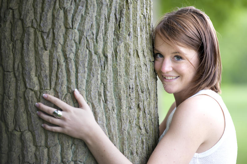 Loving nature. Young woman hugging a big tree royalty free stock image