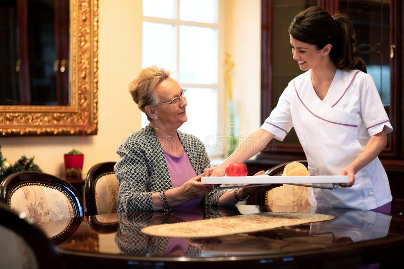 Loving nurse serving food to the occupants of the retirement home. Bringing them bringing pastry and an apple stock photography
